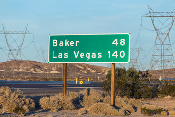 Aluminium Prints Las Vegas Late afternoon view of Las Vegas 140 miles and Baker 48 miles highway sign on I-15 near Barstow in California.