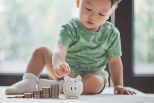 baby putting dollar coin in piggy bank,saving concept.