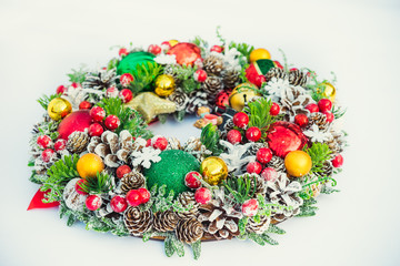 Beautiful traditional bright Christmas wreath decorated with pine cones, spruce branches,berries, balls, stars, decorative beers on white background isolated. Close up, selective focus. Copy space.