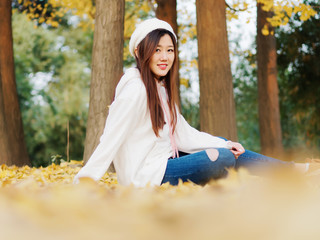 Portrait of beautiful Chinese young girl wearing white hoodie and blue jeans sitting in foliage in autumn park and smiling at camera. Outdoor fashion portrait of glamour cute stylish lady.