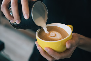 Closeup image of female hands pouring milk and preparing fresh latte, coffee artist and preparation concept, morning coffee