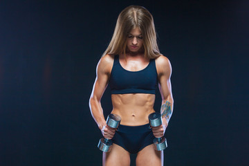 Muscular and sexy girl with long hair in black clothes with dumbbells of steel color. Fitness, healthy lifestyle concept. Isolated on the black background. Close up.