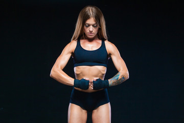 Black boxing bandages on the hands of a muscular girl in black clothes. Boxing, kickboxing, karate. Fitness, healthy lifestyle concept. Isolated on the black background.
