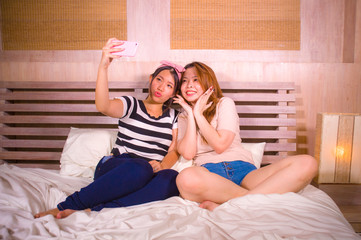 two young happy and pretty Asian Korean girlfriends sitting at home bedroom taking selfie portrait photo with mobile phone camera sitting on bed in women friendship
