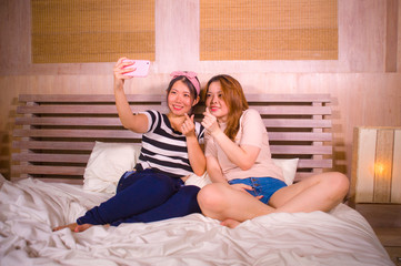 two young happy and pretty Asian Chinese girlfriends sitting at home bedroom taking selfie portrait photo with mobile phone camera sitting on bed in women friendship
