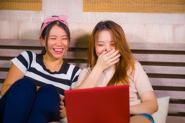 two young pretty and happy Asian Korean student girls together at home bedroom using internet social media in laptop computer laughing cheerful on bed having fun
