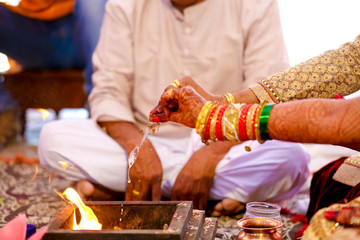 indian groom making offerings to sacred fire, indian wedding