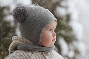 Cute little boy in winter. Kid in winter clothes walking under the snow. Pretty little baby under the falling snow