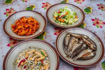 Assorted Indonesian home made food served on plates : kentang balado, sayur cap cay, ikan goreng, tumis toge tahu