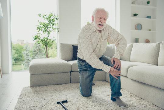 Sad tired annoyed stylish old man wearing checked shirt on carpe
