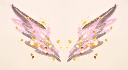Golden glitter and glittering stars on abstract pink and black watercolor wings in vintage nostalgic colors.