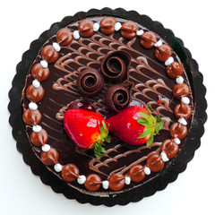 chocolate cake with strawberries on white background, top view