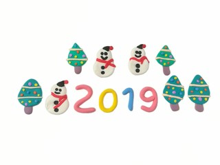 Cute snowman have sweet smile, colorful snow on tree and 2019 new year text made from plasticine clay are placed on white background, beautiful dough decorate are festival