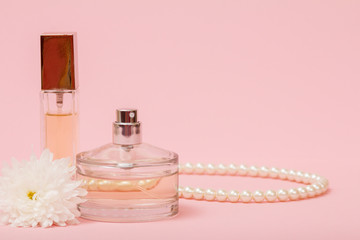 Women perfumes with beads on a pink background.
