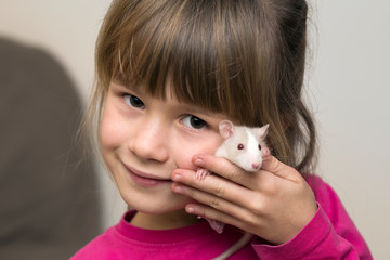 Portrait of happy smiling cute child girl with white pet mouse hamster on light copy space background. Keeping pets at home, care and love to animals concept.