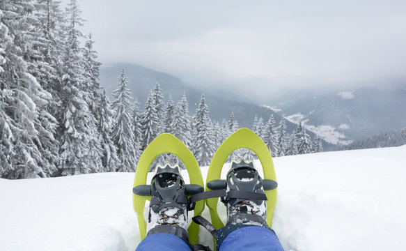 POV view of legs and trekking shoes with green snowshoes on background of mountains and snow forest.