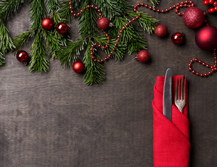 Holiday serving with fork and knife in red napkin at wood background