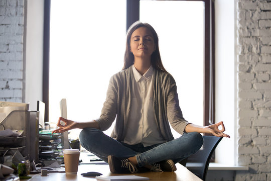 Serene calm business woman sit on office desk taking break for meditation, mindful employee doing yoga exercise in lotus pose for relaxation at workplace, no stress relief, balance at work concept