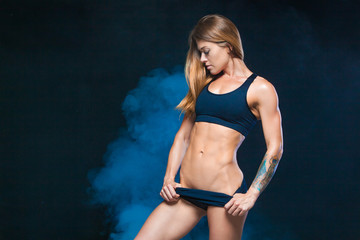Beautiful, sexy, muscular girl in black lingerie surrounded by blue smoke. Sports, gym. Fitness, healthy lifestyle concept.