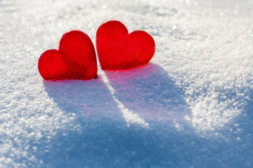Two red glass hearts on white glittering snow. Romantic consept. Love and St Valentine