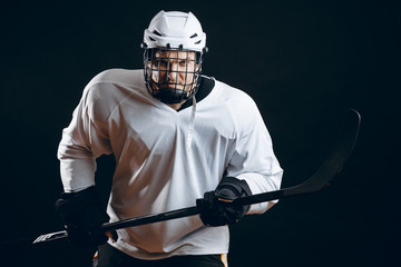 Image of ice-hockey player in white sportswear holding hockey stick prepare to defense.