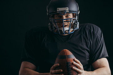Sport concept. American football sportsman player in black sports outfit on black background with copy space. Sport concept.