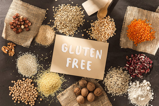 Gluten free flour and cereals millet, quinoa, corn bread, brown buckwheat, rice, bread and pasta with text gluten free in English language with spoon on wooden background, top view