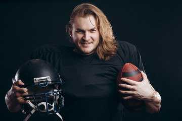 American football player with blonde loose hair in action, demonstrates the will to move forward and to win at any cost