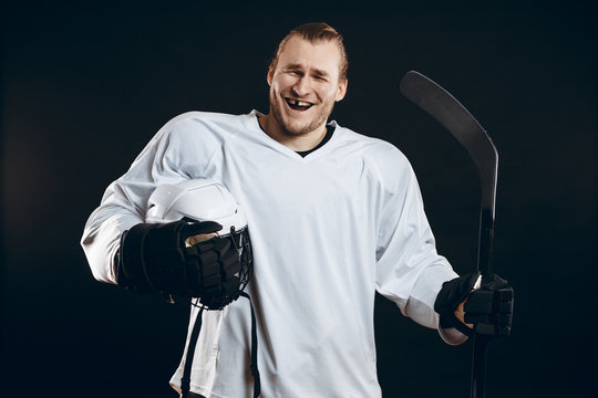 Handsome hockey player smiling at camera with one missing tooth, asking the supporters if there is so any interest in going to that hockey game