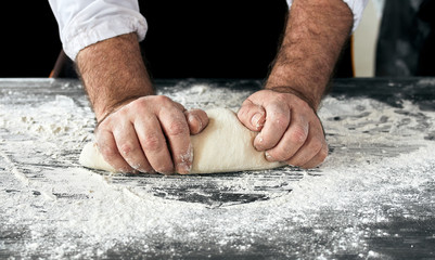 Baker hands kneading dough in the kitchen