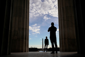 People take pictures at the Lincoln Memorial on the first day of a partial federal government shutdown in Washington