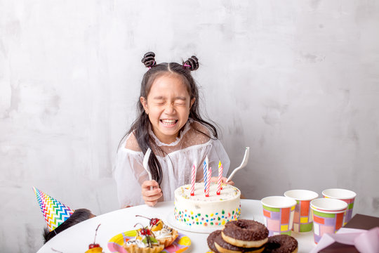 funny little beautiful girl holding forks and going to taste the cake. close up photo. copy space. wish, desire