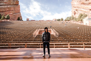 Portrait of Male Person Standing Front and Center on a Stage Dreaming and Imagining the Future while Facing Stadium Stands at Outdoor Amphitheater Concert Music Hall