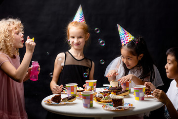 children are having fun with ssoap bubbles on holiday. isolated black background. happy event. studio shot. childhood.