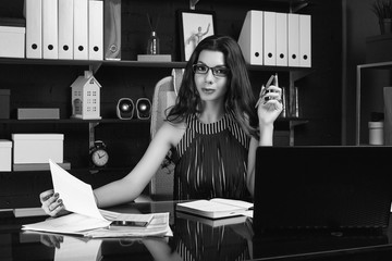 Young beautiful business woman working at stylish black desk