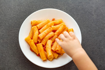 Little child eats fresh pasta with tomato sauce parmesan cheese