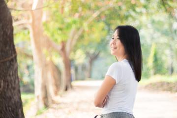 Beautiful Asian Woman Relaxing Outdoors in Green Nature Background.
