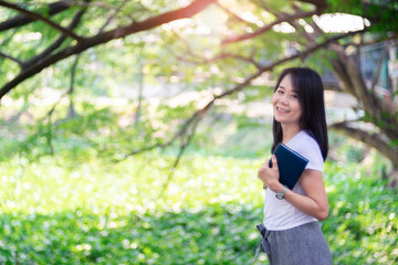 Asian woman reading book at park with green tree nature.