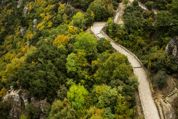 aerial photography landscape view of narrow paved and curved road for walking and promenade in mountain forest highland scenic environment tourist world heritage site in central Asia