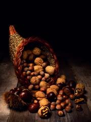 Natura morta con cornucopia, noci, nocciole e castagne