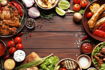 Flat lay composition with delicious barbecued meat and vegetables on wooden background. Space for text