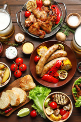 Delicious meal served for barbecue party on wooden table, flat lay