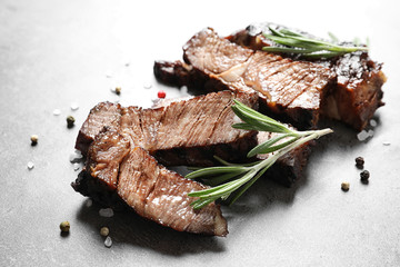 Pieces of delicious barbecued meat with rosemary on gray table