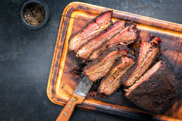 Printed kitchen splashbacks Grill / Barbecue Traditional smoked barbecue wagyu beef brisket as piece and sliced offered as top view on an old cutting board with copy space left