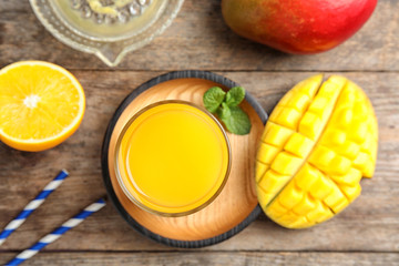 Glass of fresh mango drink and tropical fruits on wooden table, top view