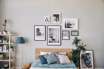 photos of different sizes in a frame hanging over the bed . Modern bedroom interior.