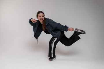 Beautiful young cute woman dancer in a blue jacket in a stylish T-shirt in fashionable black sports pants is standing on one leg in the studio on a white background. Talented girl dancing