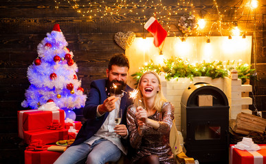 Modern Christmas Trends. New Year fashion concept. Couple in love. Christmas home interior. Cute young woman and handsome man with Santa dress.
