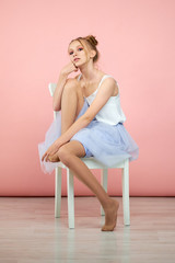 beautiful blonde girl in the image of a princess on a pink background is not sitting chair. studio portrait