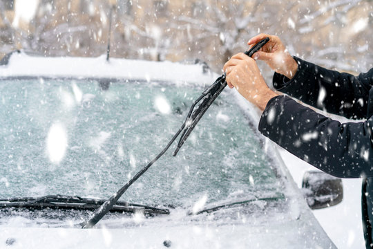 man adjusting and cleaning wipers of car in snowy weather b